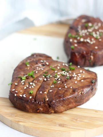Two air fryer tuna steaks garnished with sesame seed and chives.