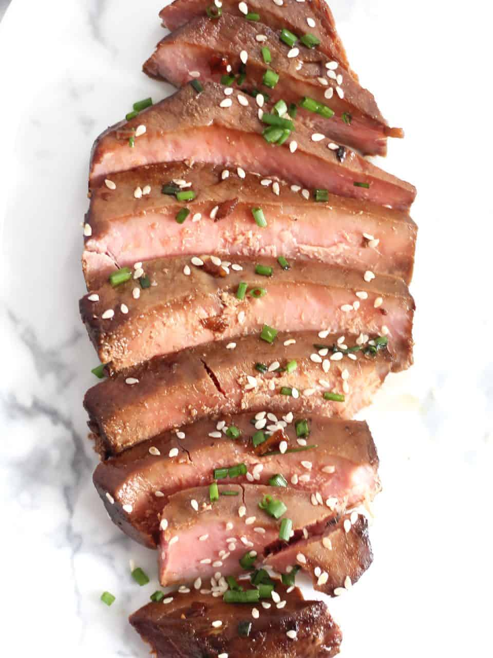 An air fryer tuna steak sliced into pieces and garnished.
