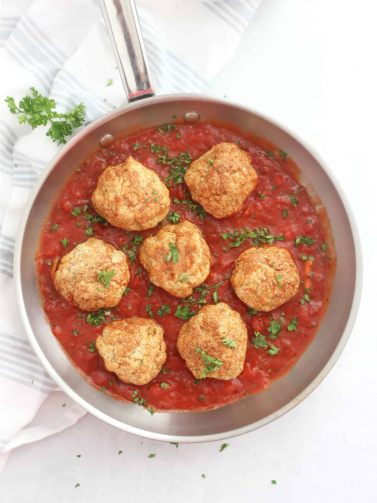 Overhead shot of seven chicken meatballs in a skillet with marinara sauce and garnished with parsley.