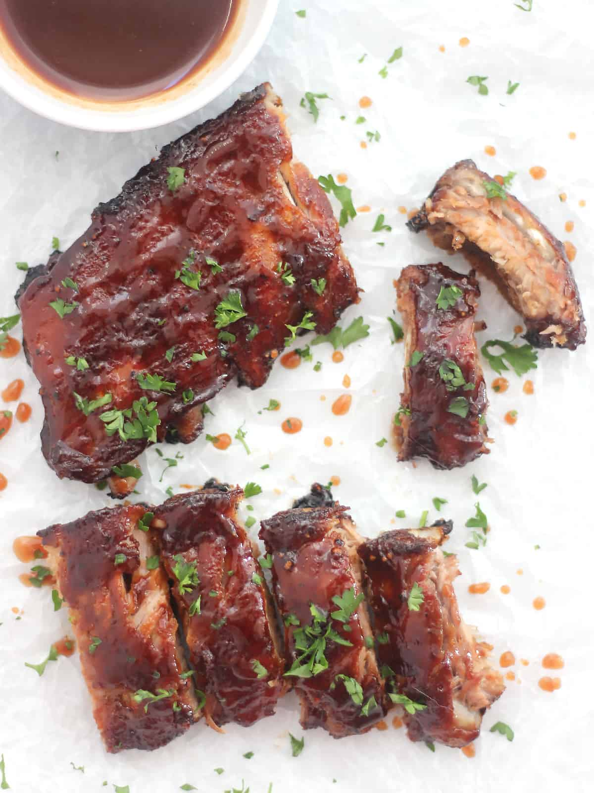 Overhead shot oven maple bbq oven roasted ribs drizzled with sauce.