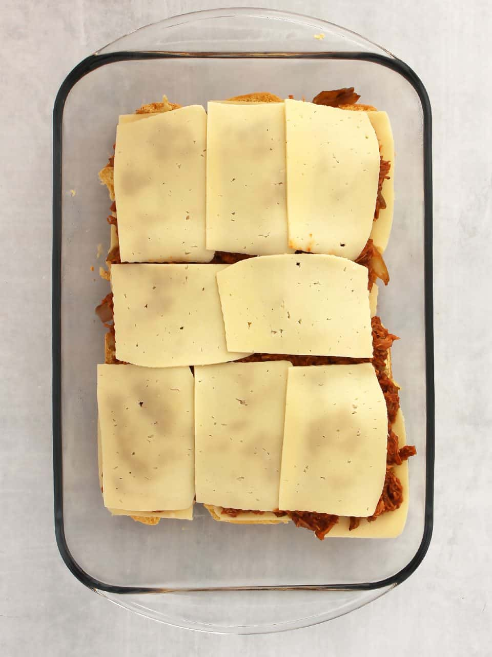 Cheese slices placed on top of the pulled pork.