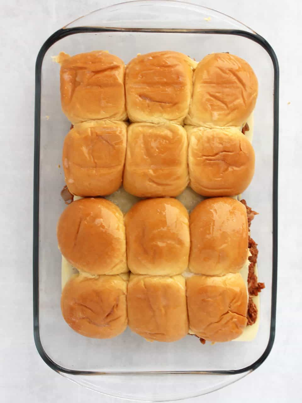 The top of the buns added to the sliders and ready to be baked.