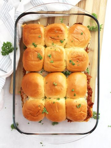 Overhead shot of twelve pulled pork sliders in a glass casserole dish garnished with fresh parsley.